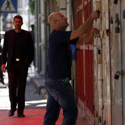A Palestinian man closes a shop in the West Bank city of Ramalla (Photo: Reuters) (Photo: Reuters)