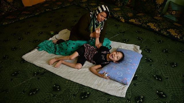 שרה מעסה את בתה (צילום: AFP) (צילום: AFP)