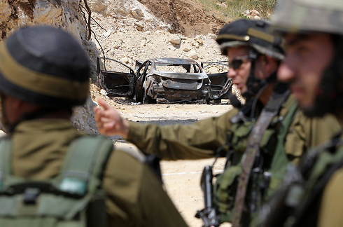 חיילים ליד הרכב השרוף שאותר בחיפושים (צילום: AFP) (צילום: AFP)