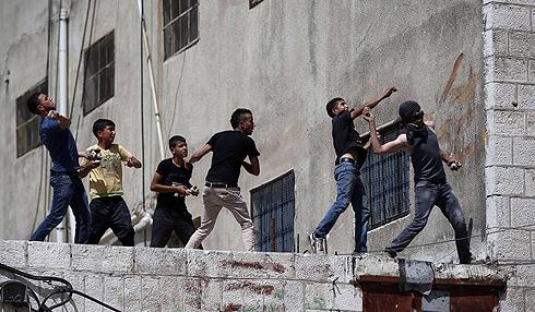"""נערים פלסטינים בחברון משליכים אבנים לעבר כוחות צה""""ל (צילום: AFP) (צילום: AFP)"""