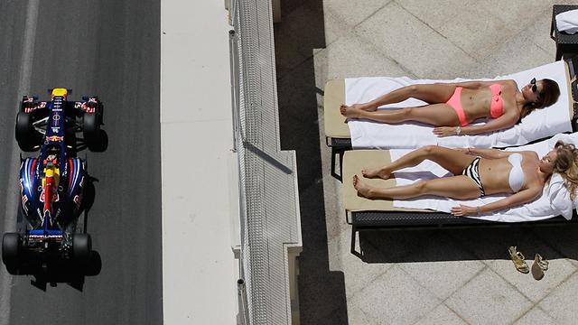 משתזפים מול האגזוזים. בנות בבריכת בית מלון על רקע מסלול פורמולה 1 שבמונקו (צילום: AP) (צילום: AP)