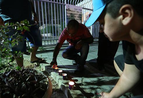 אזרחים מדליקים נרות זיכרון ליד המכון לרפואה משפטית (צילום: ירון ברנר)