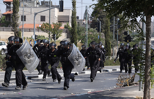 Riot police rush down an East Jerusalem street to confront protesters on Friday (Photo: Gil Yohanan) (Photo: Gil Yochanon)