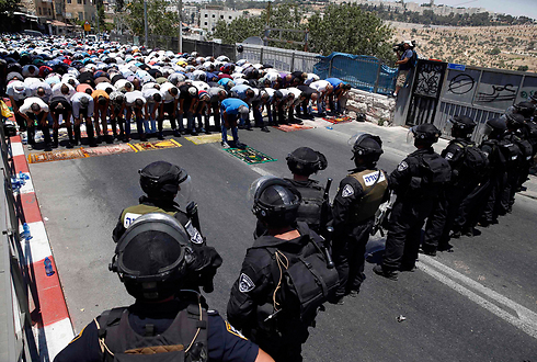 Protesters pray in front of riot police in East Jerusalem on first Friday of Ramadan. (Photo: Reuters) (Photo: Reuters)