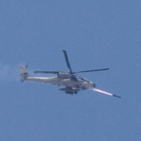 """מסוק של צה""""ל משגר טיל מעל הרצועה (צילום: AFP) (צילום: AFP)"""