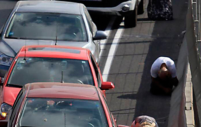 Israelis take cover on Ayalon as sirens blare in Tel Aviv (Photo: Reuters)