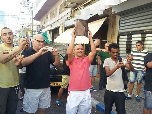 תושבים בדרום תל אביב עם חלקי רקטה ()