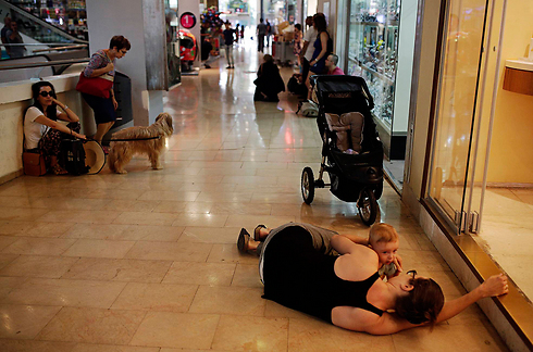 אנשים תופסים מחסה בקניון בתל אביב (צילום: רויטרס) (צילום: רויטרס)