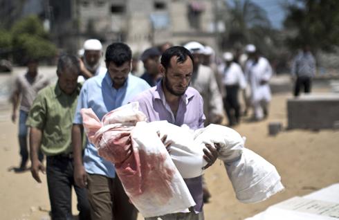 """פינוי גופתו של ילד בן חמש שנהרג בהפצצות צה""""ל בעזה (צילום: AFP) (צילום: AFP)"""