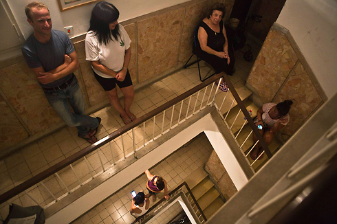 Israelis taking cover in stairwells during sirens (Photo: Reuters)