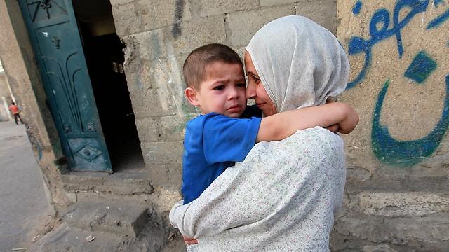 אם ובנה שעזבו את ביתם בשכונת א-זיתון במזרח עזה (צילום: EPA) (צילום: EPA)
