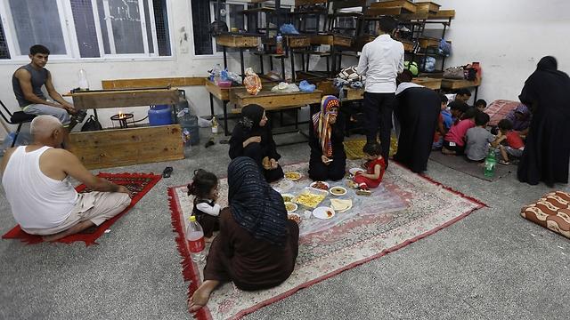 """ארוחה בבית ספר של האו""""ם שהוסב למקלט (צילום: AFP) (צילום: AFP)"""