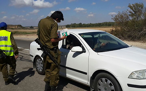 Before: IDF soldiers checking identifications at the entrance to Netiv HaAsara (Photo: George Ginsburg)