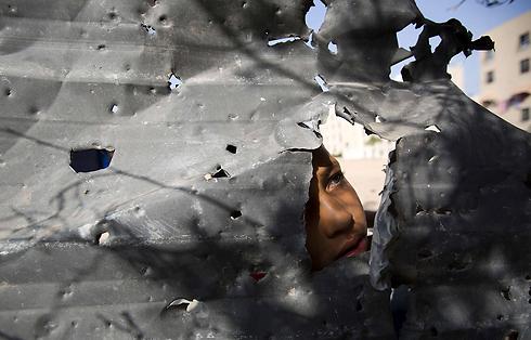 ילד בבית להיא שבצפון רצועת עזה מביט דרך הריסות (צילום: AFP) (צילום: AFP)