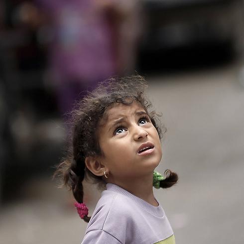 """ילדה פלסטינית מביטה במזל""""ט ישראלי ברפיח (צילום: AFP) (צילום: AFP)"""
