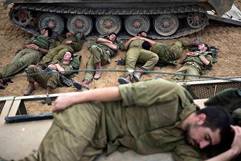 חיילי מילואים תופסים תנומה בשטח כינוס ליד הרצועה (צילום: רויטרס) (צילום: רויטרס)