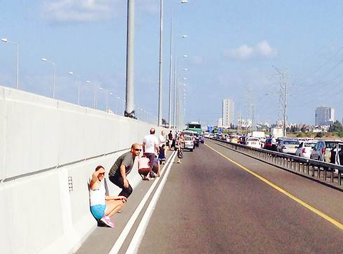 Israelis stop at the sides of the Ayalon Highway during the rocket alert siren (Photo: Tomer Cohen)