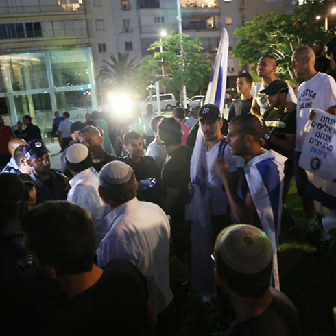 A Breaking the Silence protest and a counter-demonstration face off during Operation Protective Edge (Photo: Moti Kimchi)