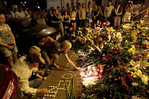 מניחים פרחים מול שגרירות הולנד בקייב (צילום: AP) (צילום: AP)