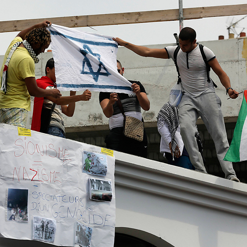 Protesters set fire to an Israeli flag during a rally in Paris against Operation Protective Edge, July 2014. (Photo: AP) (Photo: AP)