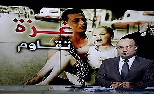 """מנחה אל-ג'זירה ומאחוריו הסמל """"עזה מתנגדת"""" (או: """"עזה נלחמת"""")"""