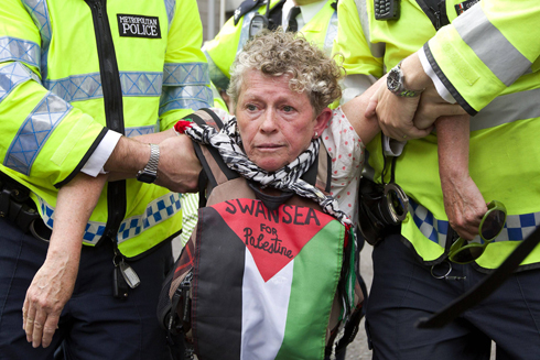 Police holding a pro-Palestinian demonstrator outside the Israeli embassy in London (Photo: AFP) (Photo: AFP)