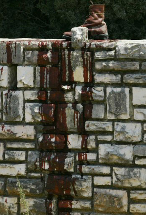 Blood-stained army boots on stone wall in Kfar Giladi, 2006 (Photo: Reuters) (Photo: Reuters)