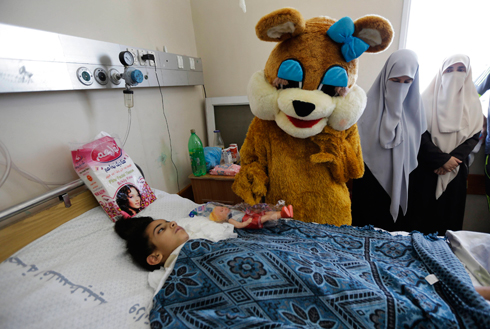 ילד שנפצע בעזה מקבל מתנה לעיד אל-פיטר (צילום: AP) (צילום: AP)
