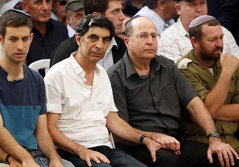 שר הביטחון יעלון, קרוב משפחה, לצד אביו של סגן הדר גולדין בהלוויה (צילום: AFP) (צילום: AFP)