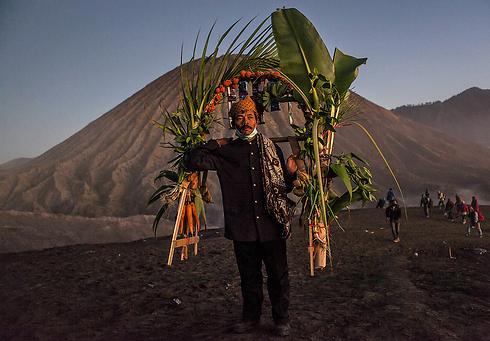 גבר נושא ירקות שישליך מראש ההר (צילום: gettyimages)
