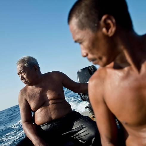 הארון (משמאל) ובנו בסירת הדיג (צילום: AFP) (צילום: AFP)