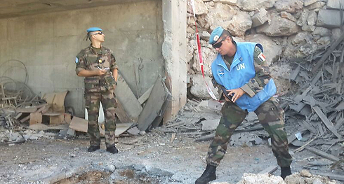 UNIFIL forces stand over hole caused by Saturday's rocket (Photo: Ahiya Raved)