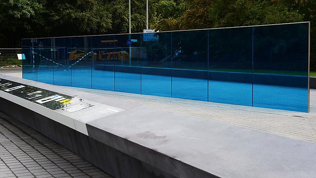 """קיר זכוכית בצבע כחול ובבסיסו פאנלים שמספרים על """"תוכנית טי-4"""". אתר ההנצחה (צילום: AFP) (צילום: AFP)"""