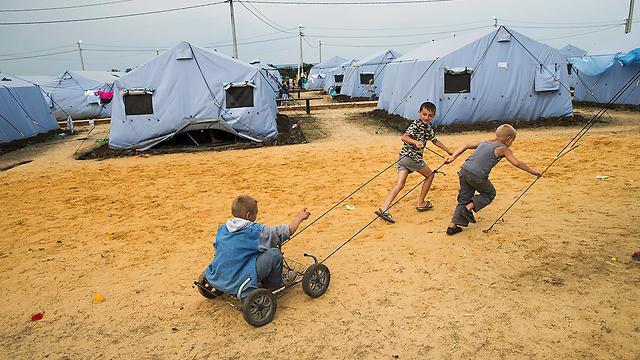 ילדים אוקראינים משחקים במחנה פליטים בעיר רוסטוב על הדון ברוסיה (צילום: AP) (צילום: AP)