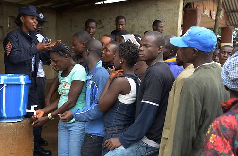 מחכים בתור לשטוף ידיים בליבריה, במאמץ למנוע את התפשטות האבולה (צילום: AFP) (צילום: AFP)