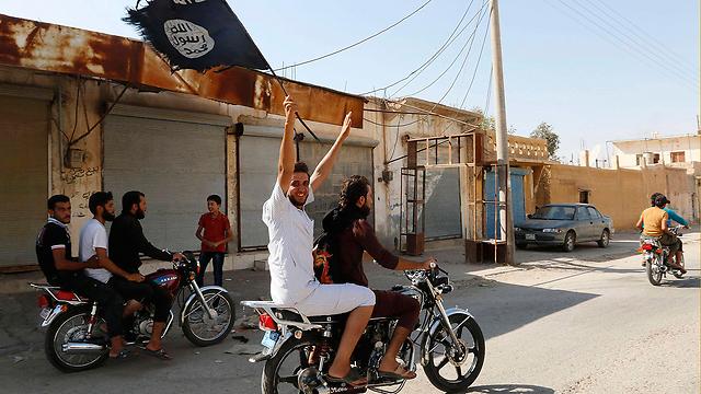 חוגגים עם דגל דאעש בא-ראקה, סוריה, באמצע העשור (צילום: רויטרס) (צילום: רויטרס)
