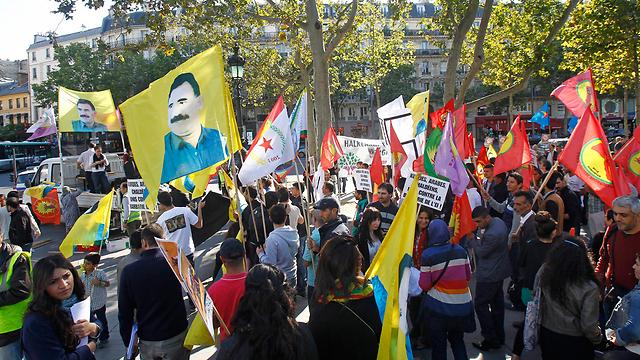 מפגינים בפריז בעד הכורדים עם דגלי אוצ'לאן (צילום: AP) (צילום: AP)