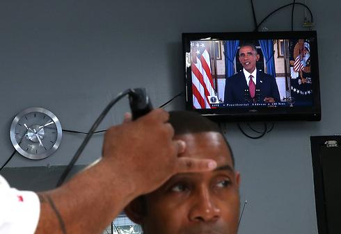 צופים בנאום, במספרה (צילום: AFP) (צילום: AFP)