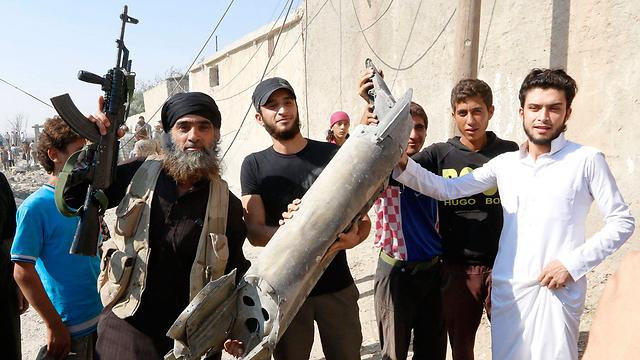 תושבים ואנשי ארגון הטרור מציגים את שברי המטוס (צילום: רויטרס) (צילום: רויטרס)
