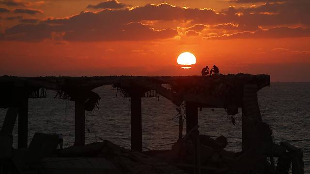 Palestinians sit atop a damaged building on a beach during sunset in the northern Gaza Strip (Photo: Reuters) (Photo: Reuters)