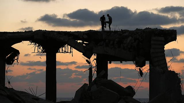 Palestinians atop destroyed building in the Gaza Strip (Photo: Reuters)