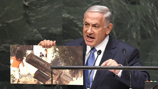 Netanyahu presenting photo of Palestinian children playing near a rocket launcher (Photo: AFP)