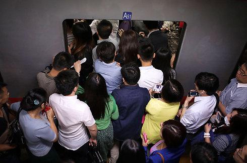 רצים לתפוס מקום על הרכבת כדי לא לאחר לעבודה. העומס ברכבת בבייג'ינג (צילום: AP) (צילום: AP)