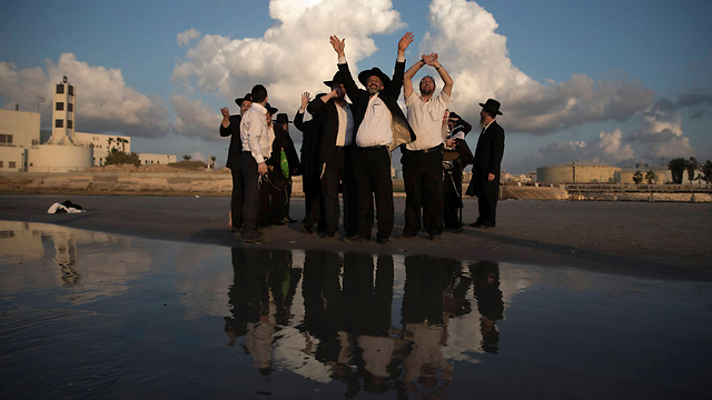 Haredi men practice Yom Kippur Tashlikh prayer in Tel Aviv (Photo: Reuters)