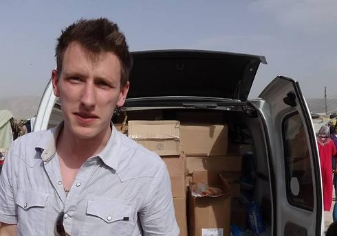 קסיג במהלך עבודתו בסוריה, על רקע משאית מלאה בציוד לנזקקים (צילום: AP) (צילום: AP)