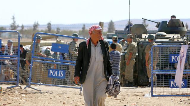A Syrian man flees across the Turkish border to escape the Islamic State bombardment of Kobani. (Photo: AP) (Photo: AP)