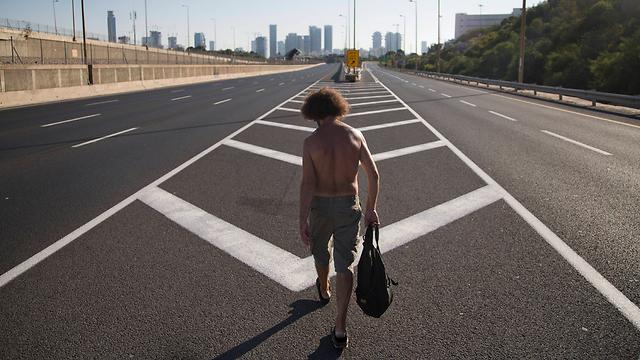 A man walks down the vehicle-free Ayalon highway in Tel Aviv (Photo: AP)