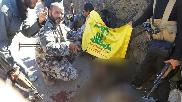 Hezbollah soldiers near the dead body of an armed militant