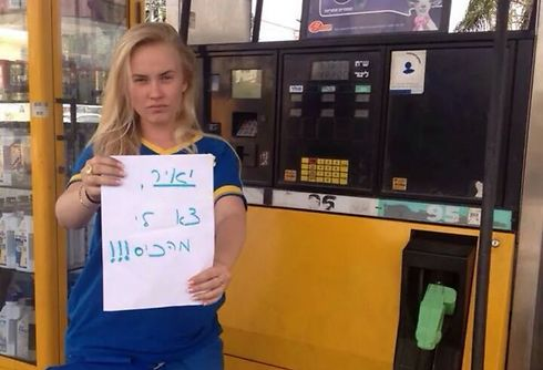 """Gas station employee holding a sign that says """"Yair, get out of my pocket"""""""