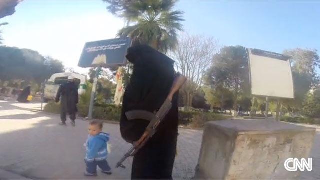 עם רובה קלצ'ניקוב ונגד נשים בלבוש לא הולם. משטרת הנשים של דאעש ברקה (צילום: CNN) (צילום: CNN)